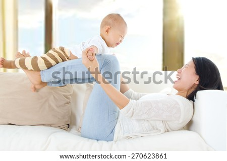 Asian mother lifting up her baby with legs