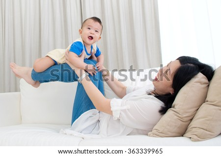 Asian mother lifting up her baby with legs - stock photo