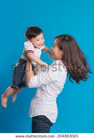 asian mother picking up her baby boy - stock photo