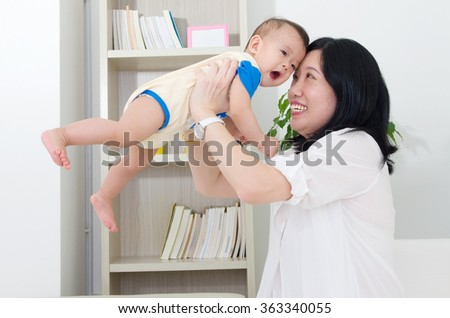Asian mother playing with her baby - stock photo
