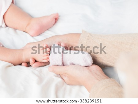 Asian mother putting the socks on her little baby on white bed.