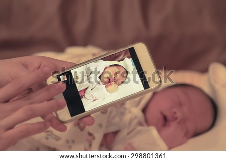 Asian mother take a photo of her baby female son with smart phone focused on the device this image is for Asian.baby in Asian family or.Asian mother.Asian female.Asian woman.Asian kid.Asian newborn. - stock photo