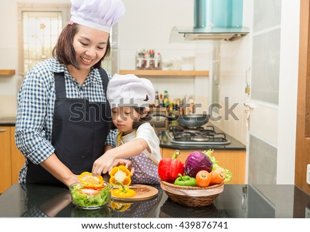 Asian mother teaching daughter making salad in kitchen,Cooking  concept of happy asian little girl and mother making salad for dinner and chopping paprika on cutting board with knife in kitchen - stock photo