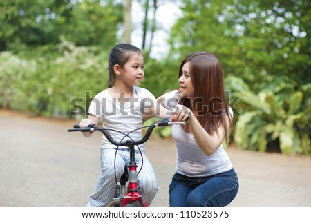Asian mother teaching little girl to ride a bike - stock photo