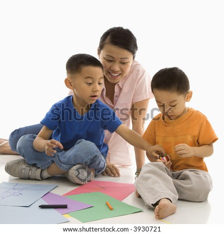 Asian mother with boys coloring. - stock photo
