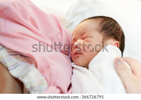 Asian mother with newborn baby in the hospital - stock photo