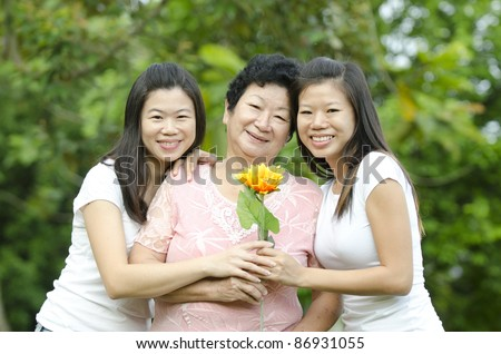 asian mother with two of her daughters - stock photo