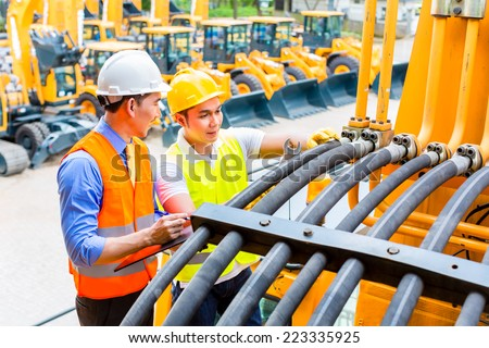 Asian motor mechanic discussing with engineer task list in construction machine workshop - stock photo