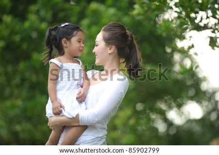 Asian mum and daughter enjoying each others company in the park - stock photo