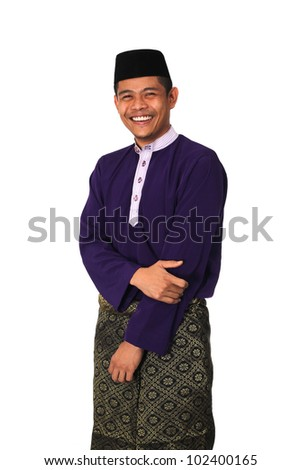 Asian muslim male with traditional Malay costume in smiling action, Baju Melayu - stock photo