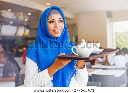 asian muslim waitress holding a tray with tea. Woman wearing hijab working in cafe - stock photo