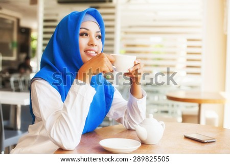 asian muslim woman enjoying a cup of tea - stock photo