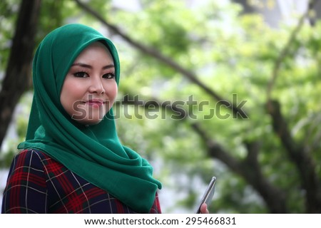 Asian muslimah wearing hijab in green park area with copy space area for advertising material - stock photo