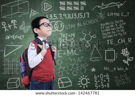Asian nerd boy posing with backpack in class - stock photo