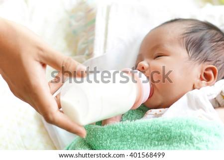 Asian newborn baby drinking milk from bottle - stock photo