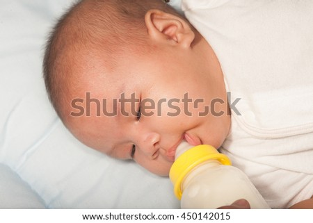 Asian newborn baby drinking milk from bottle.