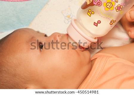 Asian newborn baby drinking milk from bottle. - stock photo
