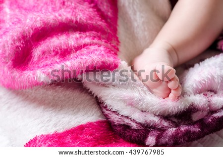 Asian newborn baby's foot on the bed - stock photo
