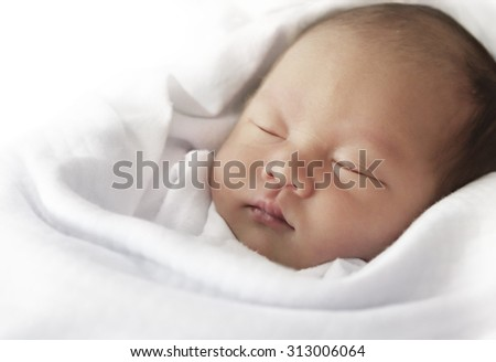 Asian newborn baby sleeping on white towel post processing with desaturated filter