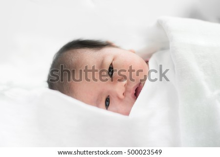 Asian newborn boy sleeping over his white bed covered with a blanket. Two day old newborn boy.
