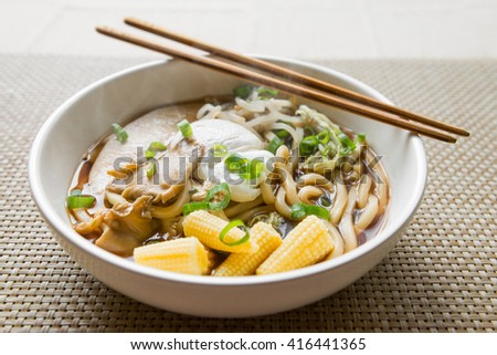 Asian noodle soup steaming in a bowl with chopsticks - stock photo
