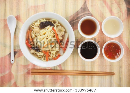 Asian noodle soup with vegetables and various sauces - stock photo
