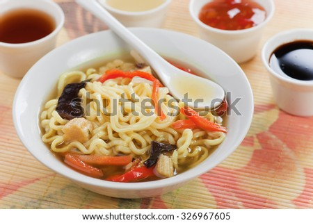Asian noodle soup with vegetables served in bowl with various sauces
