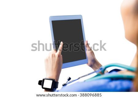 Asian nurse using tablet on white background - stock photo