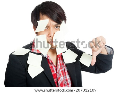 Asian office man covered in blank notes with his thumbs down  isolated on white background - stock photo