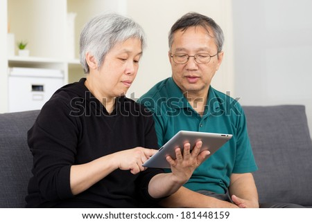 Asian old couple using tablet - stock photo