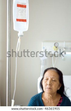 asian old woman get infusion during inpatient treatment at the hospital - stock photo