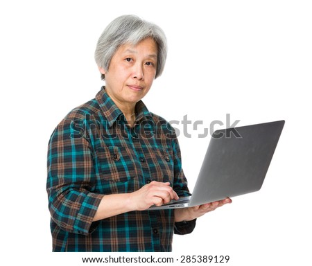Asian old woman use of notebook computer - stock photo