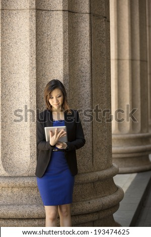 Asian or Chinese woman. Professional Lawyer or businesswoman outside a Colonial building using a digital tablet PC.  - stock photo