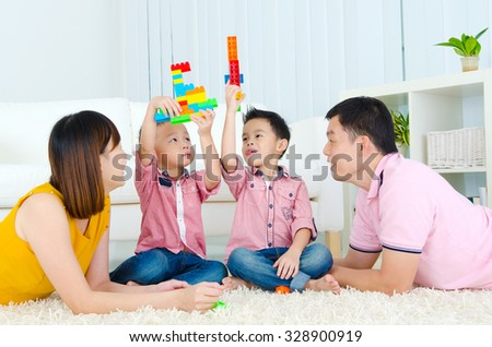Asian parent accompanied kids playing building blocks - stock photo