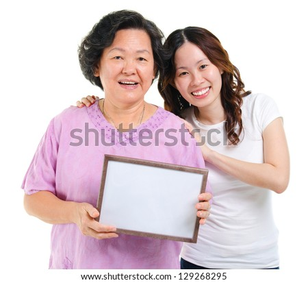 Asian parent and adult offspring holding a blank board smiling, isolated on white background - stock photo
