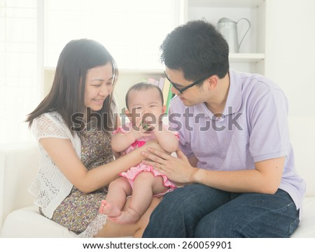 asian parent playing with baby girl in livingroom - stock photo