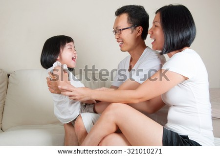 Asian parent playing with their daughter at home