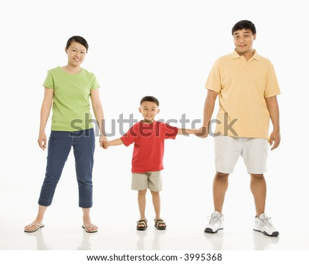 Asian parents holding hands with son in front of white background. - stock photo