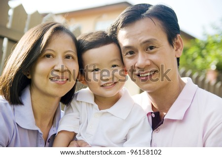 Asian parents hugging their son