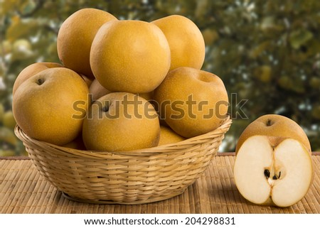 Asian pears in a basket over a wooden surface on a pear field background - stock photo