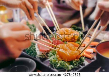 Asian people eating sashimi set in Asian restaurant - stock photo