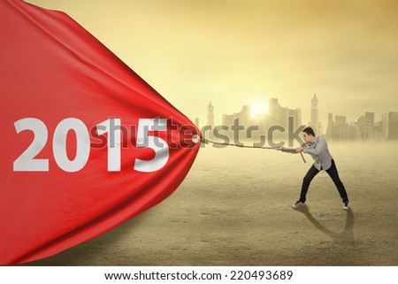 Asian person dragging number 2015 on a big banner at sunset - stock photo