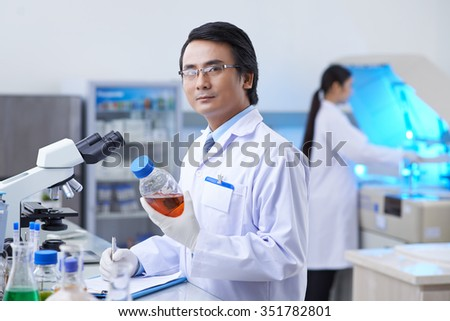 Asian pharmaceutical chemist with a bottle with medical liquid