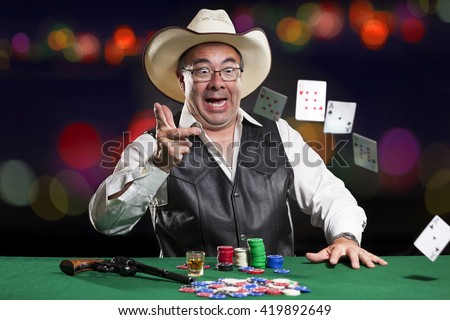 Asian Poker Player wearing cowboy hat.  Cowboy is throwing cards and has a glass of whiskey and a gun on the gaming table.  Background is dark with blurred lights. - stock photo