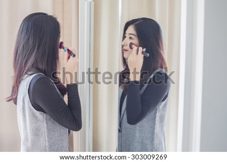 Asian portrait beautiful woman making make-up with brush on face near mirror - stock photo