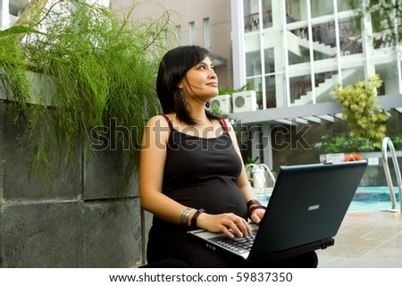 Asian pregnant business woman happy working with laptop - stock photo
