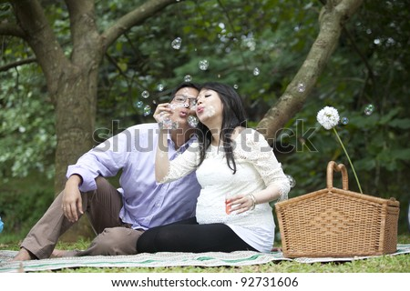 Asian pregnant couple blowing bubbles in the park - stock photo