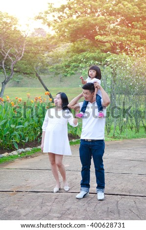 Asian pregnant woman walking in the park together with husband and daughter - stock photo