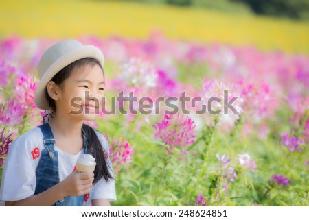 Asian pretty little girl eating an ice cream outdoors - stock photo