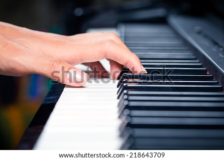 Asian professional pianist playing piano in recording studio